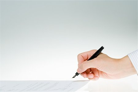 Person signing paper Stock Photo - Premium Royalty-Free, Code: 614-02838795