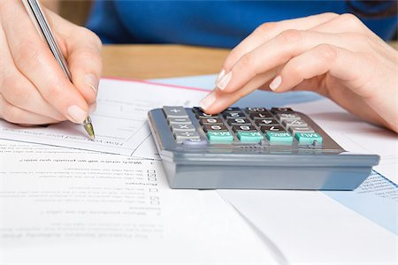 Person with calculator and forms Stock Photo - Premium Royalty-Free, Code: 614-02934395