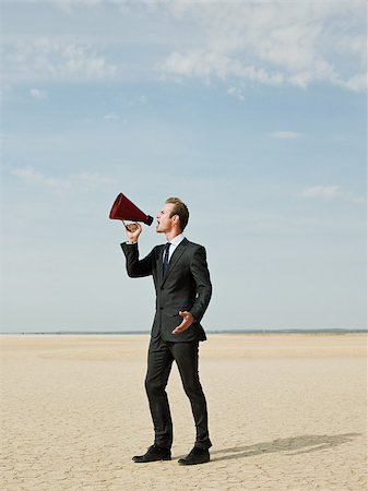 Businessman using a megaphone in the desert Stock Photo - Premium Royalty-Free, Code: 614-02984472