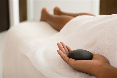 Woman on massage table holding stone Stock Photo - Premium Royalty-Free, Code: 614-02983921