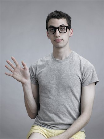 quirky - Young man waving Stock Photo - Premium Royalty-Free, Code: 614-03191033