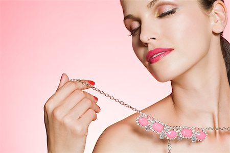 expensive jewelry - Young woman holding necklace Stock Photo - Premium Royalty-Free, Code: 614-03191308