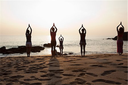 Women practicing yoga on beach at sunset Stock Photo - Premium Royalty-Free, Code: 614-03420405