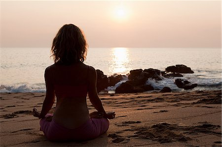 Woman practicing yoga on beach at sunset Stock Photo - Premium Royalty-Free, Code: 614-03420407