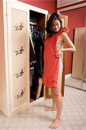 Young woman choosing clothes Stock Photo - Premium Royalty-Free, Code: 614-03468813