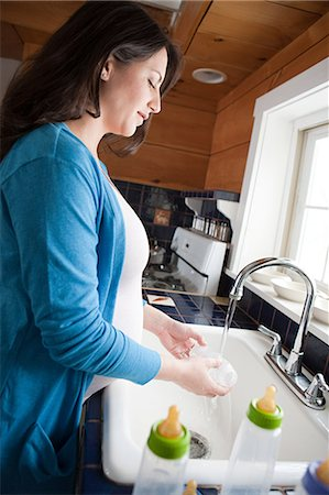Pregnant woman washing baby bottles Stock Photo - Premium Royalty-Free, Code: 614-03506471