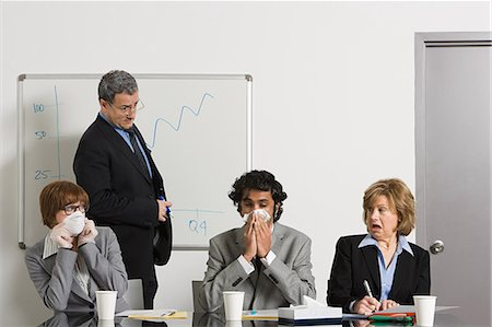 Businessman blowing nose in office Stock Photo - Premium Royalty-Free, Code: 614-03507042