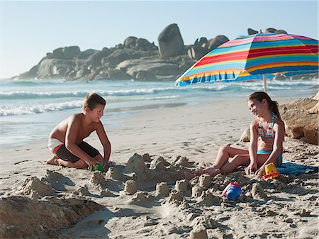 Boy and girl making sandcastles on beach Stock Photo - Premium Royalty-Free, Code: 614-03507161