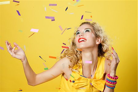 Young blonde woman with colourful confetti Stock Photo - Premium Royalty-Free, Code: 614-03507561
