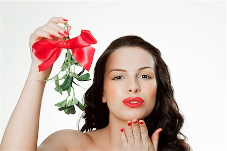 Young woman blowing a kiss holding mistletoe Stock Photo - Premium Royalty-Free, Code: 614-03507571