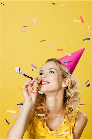Young woman wearing party hat with party blower and confetti Stock Photo - Premium Royalty-Free, Code: 614-03507572