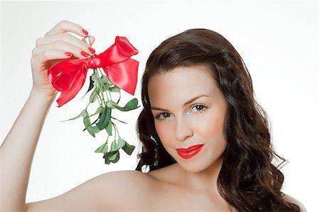 Young woman holding mistletoe Stock Photo - Premium Royalty-Free, Code: 614-03507604