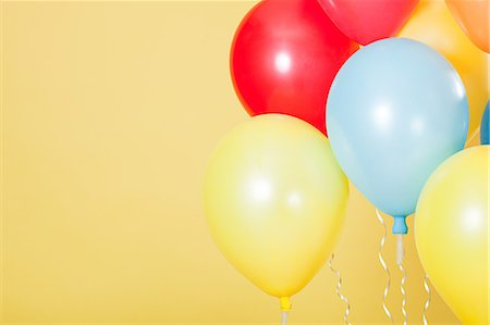 Colourful party balloons against yellow background Stock Photo - Premium Royalty-Free, Code: 614-03507605