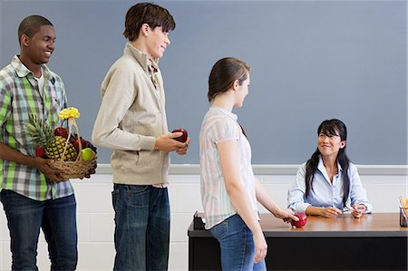 High school student giving teacher an apple Stock Photo - Premium Royalty-Free, Code: 614-03551990