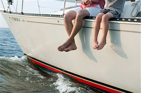 Father and son sitting on yacht, legs dangling Stock Photo - Premium Royalty-Free, Code: 614-03647942