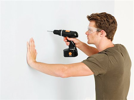 drilling - Young man using electric drill Stock Photo - Premium Royalty-Free, Code: 614-03648155