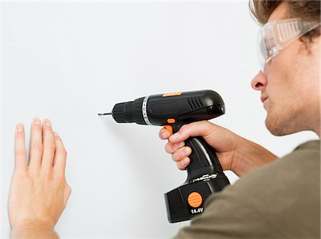 drilling - Young man using electric drill Stock Photo - Premium Royalty-Free, Code: 614-03648197
