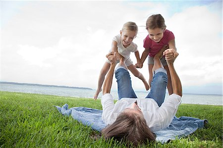 Daughters balancing on feet of mother Stock Photo - Premium Royalty-Free, Code: 614-03648743