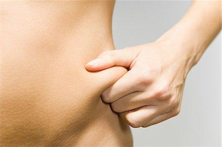 Woman pinching her hip Stock Photo - Premium Royalty-Free, Code: 614-03649034