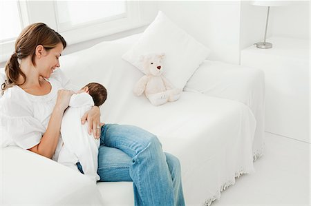 Mother breast feeding baby on sofa Stock Photo - Premium Royalty-Free, Code: 614-03684108