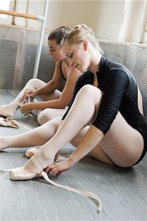 Ballerinas putting on ballet slippers Stock Photo - Premium Royalty-Free, Code: 614-03684378