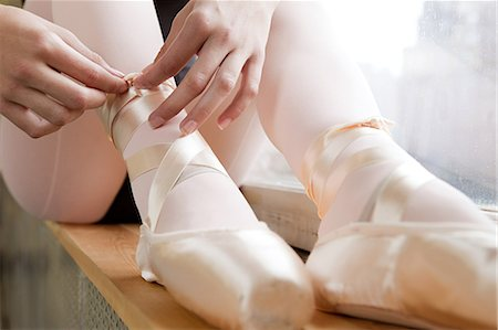 Girl tying ballet shoes Stock Photo - Premium Royalty-Free, Code: 614-03684402