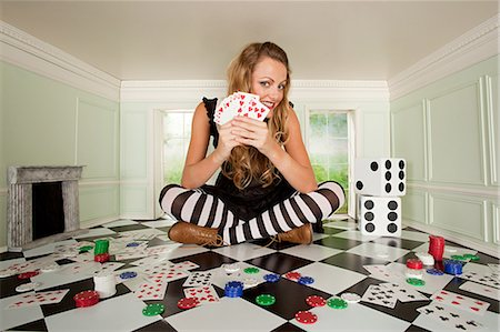 Young woman in small room with playing cards and dice Stock Photo - Premium Royalty-Free, Code: 614-03684540