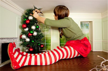 Young woman in small room decorating christmas tree Stock Photo - Premium Royalty-Free, Code: 614-03684541