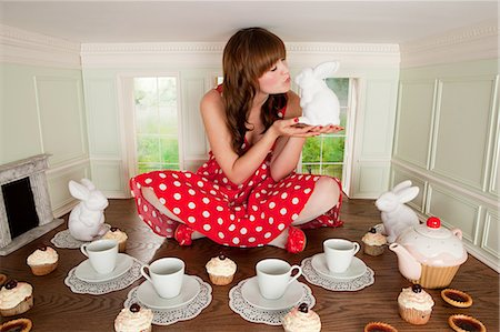 Young woman kissing rabbit at tea party in small room Stock Photo - Premium Royalty-Free, Code: 614-03684564