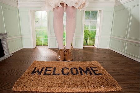 Legs of a woman and welcome mat in small room Stock Photo - Premium Royalty-Free, Code: 614-03684563