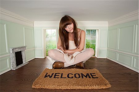 quirky - Young woman sitting in small room with welcome mat Stock Photo - Premium Royalty-Free, Code: 614-03684575