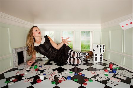 Young woman in small room throwing playing card Stock Photo - Premium Royalty-Free, Code: 614-03684573
