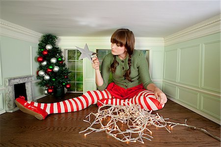 Young woman in small room with christmas decorations Stock Photo - Premium Royalty-Free, Code: 614-03684586