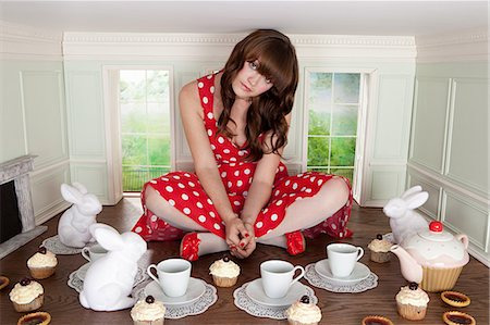 Young woman having tea party in small room Stock Photo - Premium Royalty-Free, Code: 614-03684588
