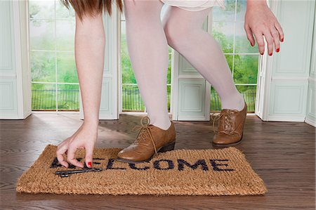 Woman picking up key on welcome mat in small room Stock Photo - Premium Royalty-Free, Code: 614-03684582