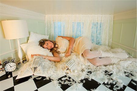Young woman sleeping amongst pillow feathers in small room Stock Photo - Premium Royalty-Free, Code: 614-03684583