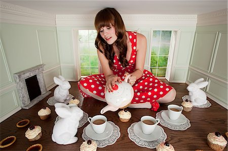 Young woman having tea party in small room Stock Photo - Premium Royalty-Free, Code: 614-03684595