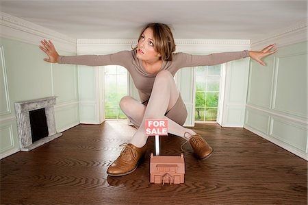 Young woman in small house with model of house for sale Stock Photo - Premium Royalty-Free, Code: 614-03684597