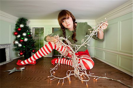 Young woman in small room with christmas lights Stock Photo - Premium Royalty-Free, Code: 614-03684598