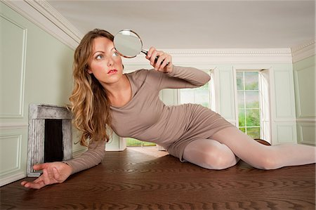 Young woman in small room with magnifying glass Stock Photo - Premium Royalty-Free, Code: 614-03684591