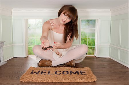 quirky - Young woman in small room with key and welcome mat Stock Photo - Premium Royalty-Free, Code: 614-03684593
