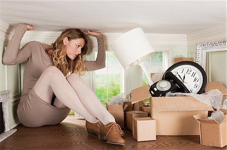 Young woman with box of objects in small room Stock Photo - Premium Royalty-Free, Code: 614-03684600