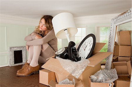 Young woman with box of objects in small room Stock Photo - Premium Royalty-Free, Code: 614-03684611