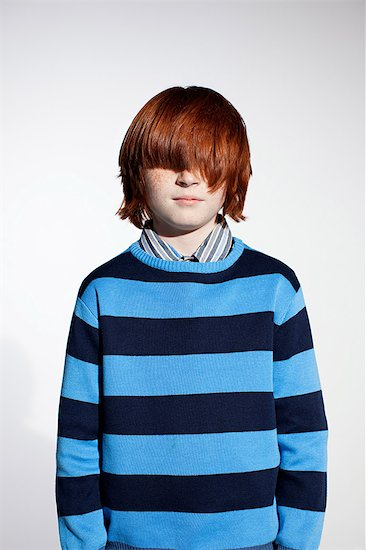 Boy in striped sweater with hair covering his eyes Stock Photo - Premium Royalty-Free, Image code: 614-03684796