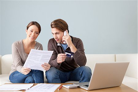 person on phone with credit card - Young couple using computer and doing paperwork Stock Photo - Premium Royalty-Free, Code: 614-03697203