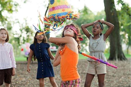 Girl at birthday party hitting pinata Stock Photo - Premium Royalty-Free, Code: 614-03697222