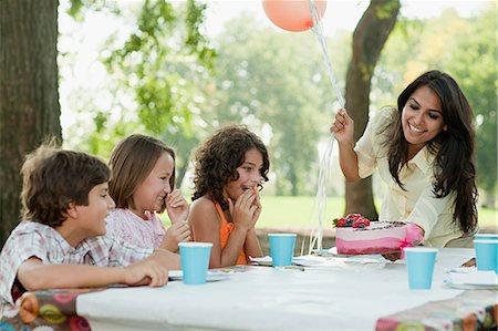 Children at birthday party with birthday cake Stock Photo - Premium Royalty-Free, Code: 614-03697231