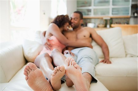 Couple on sofa, focus on feet in foreground Stock Photo - Premium Royalty-Free, Code: 614-03697296