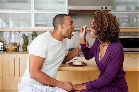 Woman feeding cake to boyfriend Stock Photo - Premium Royalty-Free, Code: 614-03697319