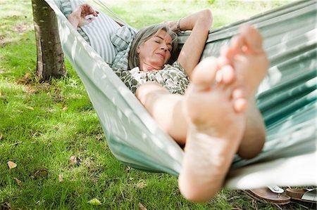 Mature woman sleeping barefoot in hammock Stock Photo - Premium Royalty-Free, Code: 614-03697394